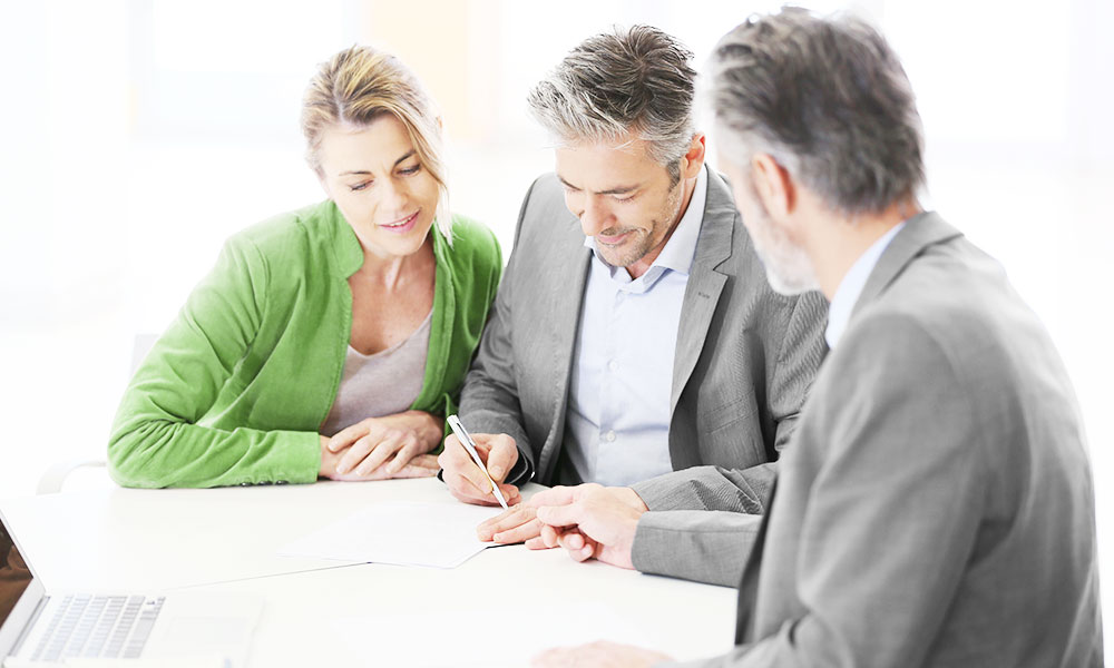 Business team discusses while writing with pen on paper