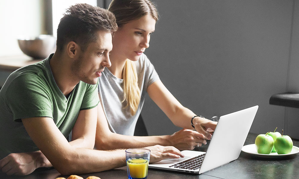 Couple looks at laptop and points at something