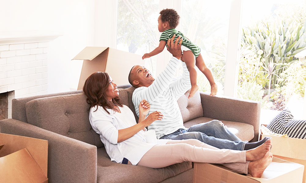 Middle aged couple playing with baby while on couch