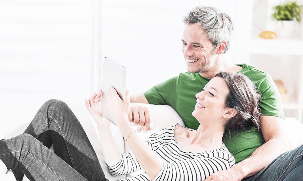 Couple lays on couch while on iPad