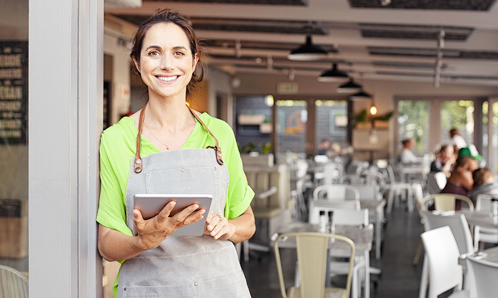Female restaurant worker smiles at camera while holding iPad