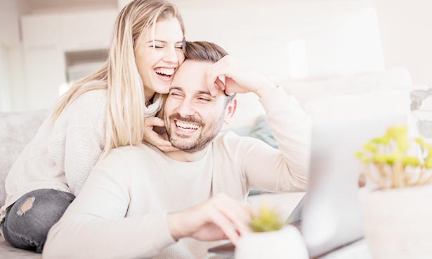 Young couple having lots of fun while on computer and smiling