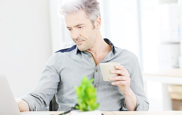Man holding a cup while looking at the computer