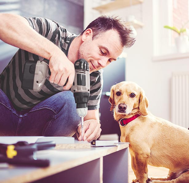 Man drilling nail into piece of wood while dog watches