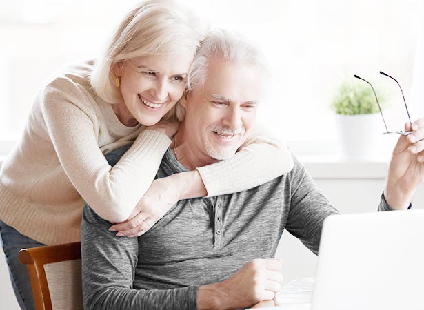 Elderly man holds glasses while wife hugs him while smiling at laptop