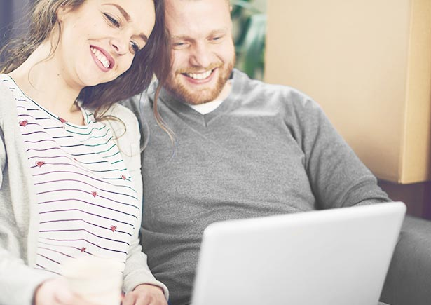 Couple smiles while looking at laptop