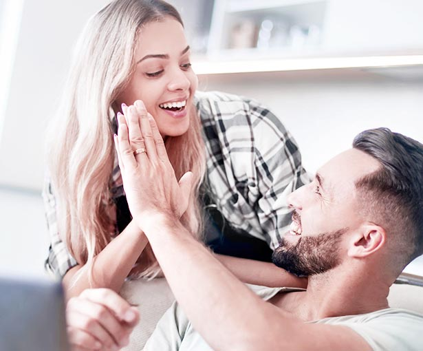 Young couple high fiving while on couch
