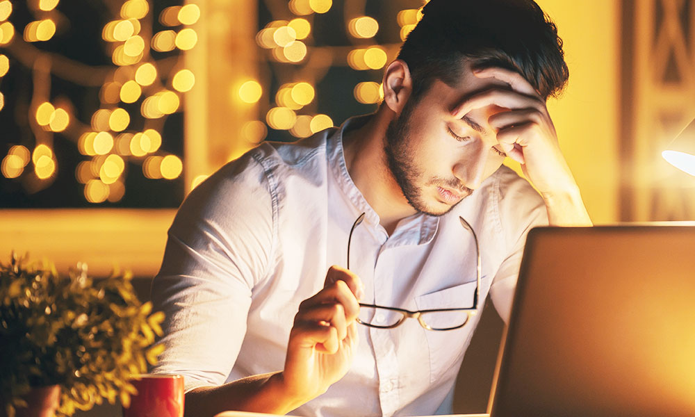 Millenial stressed out holding glasses late at night on computer