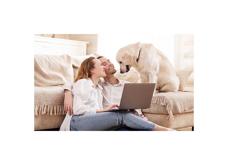 Young couple on computer laying against couch with dog