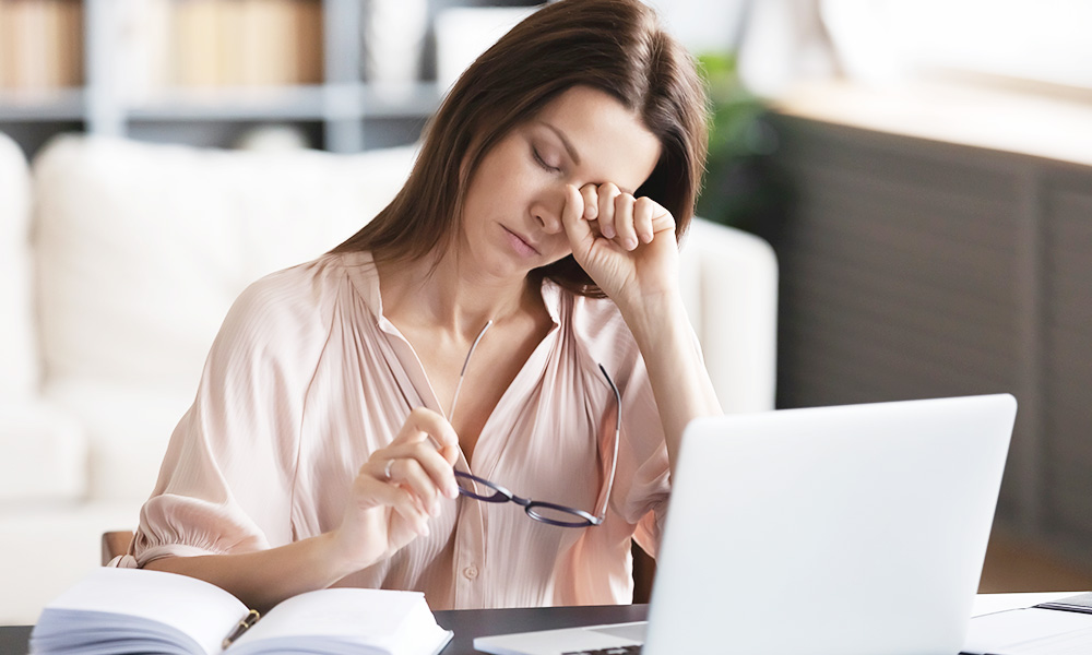 Woman stressed out and rubbing eye while dealing with tax debt