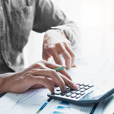 Man dealing with finances with calculator and green pencil