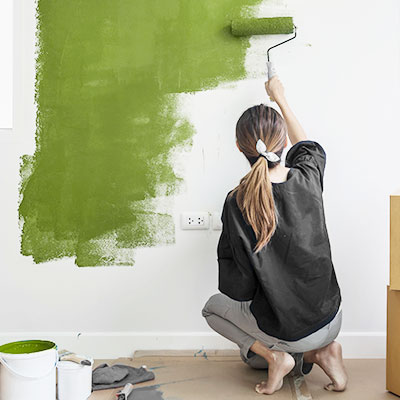 Woman Painting Wall Green with roller